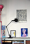 Artworks and lamps on low sideboard