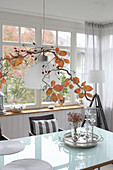 Rose hips and branch with leaves above the dining table as autumn decorations