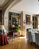 Paintings on walls with stucco details in classic dining room