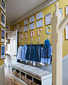 Letters and certificates above school uniforms hung from wall hooks and storage bench in hall