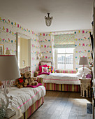 Twin beds with striped frames in children's bedroom with bird-patterned wallpaper