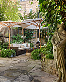 Statue, lounge furniture and parasols in courtyard garden