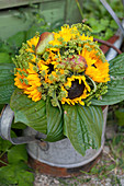 Autumn bouquet of sunflowers, fennel umbels, pears and hosta leaves in watering can