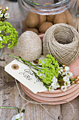 Egg covered in twine, green viburnum and saxifrage flowers