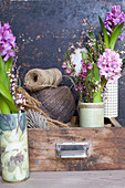 Vases of hyacinths, waxflowers and broom in drawer with balls of twine