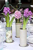 Vases of hyacinths, waxflowers and broom decorating table