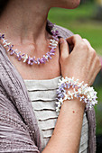 Woman wearing necklace and bracelet of threaded lilac florets