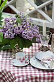 Vase of lilac and cow parsley decorating table and napkin ring made from lilac florets