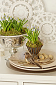 Easter decorations with grape hyacinths, Easter eggs, birds, and silver cutlery