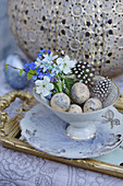 Small Easter decoration with a bouquet of forget-me-nots, cherry blossoms, and Puschkinia in a vase with Easter eggs and feathers