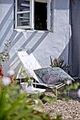 Liegestuhl mit Kissen unter Fenster auf Kiesboden