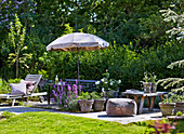 Terrace with outdoor furniture, flowers and sunshade in summer garden