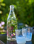Herb-flavoured water in a bottle and two glasses
