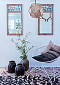 Floor vases and metal armchairs with cushions on brocante carpet, vintage mirror on the wall