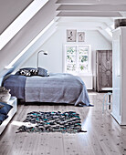Double bed with bedspread and white wardrobe in bedroom