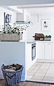White fitted kitchen over-corner, basket with firewood in the foreground