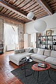 Helles Sofa und Tische im Wohnzimmer mit Holzbalkendecke