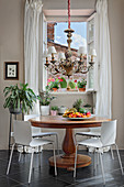 Ornate chandelier above plate of fruit on round antique table and houseplants in background