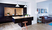 Contemporary kitchen with black cupboard fronts and free-standing counter