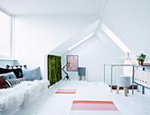 Sitzbank mit Kissen und Fell in hellem Dachzimmer
