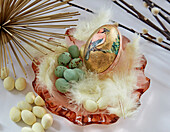Easter egg with bird motif, sugar eggs and feathers in glass bowl