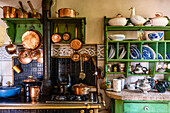 Rural kitchen with hanging copper pans and plate rack