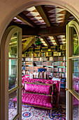 Upholstered bench with pink cover and desk in the library
