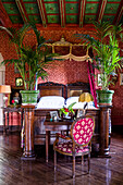 Antique double bed and indoor palm trees in the bedroom with red wallpaper