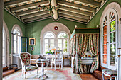 Bed behind curtain in green painted room with antique tables and chairs