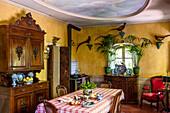 Esstisch und antike Anrichte in Wohnküche mit gelben Wänden