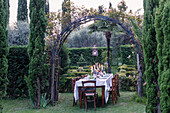 Festively set table and chairs under round arch in Renaissance garden
