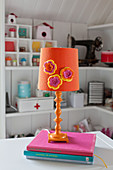 Orange table lamp decorated with crocheted flowers