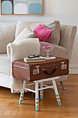 Side table made from old suitcase and stool with chair socks