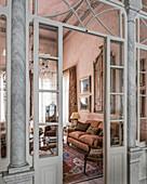 View through open lattice door into opulent pink living room
