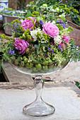 Arrangement of roses, tufted vetch, elderflowers and unripe apples in glass goblet