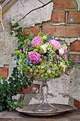 Arrangement of roses and tufted vetch in glass goblet