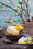 Handmade cardboard Easter eggs in nest of twigs with narcissus and grape hyacinth flowers