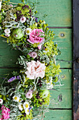 Summer wreath of roses, lady's mantle, chamomile, green apples and tufted vetch