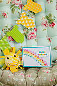 Invitation with rainbow and paper garland onesies