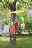 Homemade mobile with colorful hot air balloons in the garden