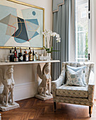Home bar on console table borne by two sphinxes in living room