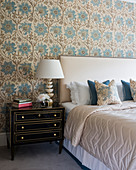 Black bedside cabinet in classic bedroom with patterned wallpaper