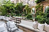 Masonry bench on elegant terrace in courtyard garden with mirrors on end wall