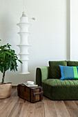 Hanging lamp above old wooden chest between green upholstered sofa and indoor plant
