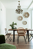 Dining table with various chairs and decorative wall plates in bright room