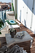 Table and wooden chair on sunny terrace on upper floor
