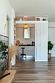 View into kitchen with door made of wooden slats