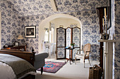 Classic bedroom with blue-and-white wallpaper and ensuite bathroom