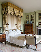 Half-tester bed in classic bedroom with panelled walls
