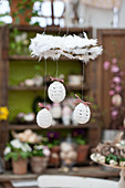 White, crocheted Easter eggs hanging from wreath of feathers